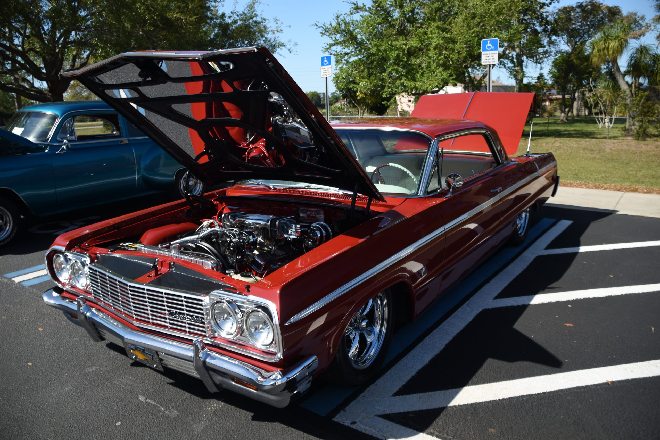 Red Chevy Impala with hood up