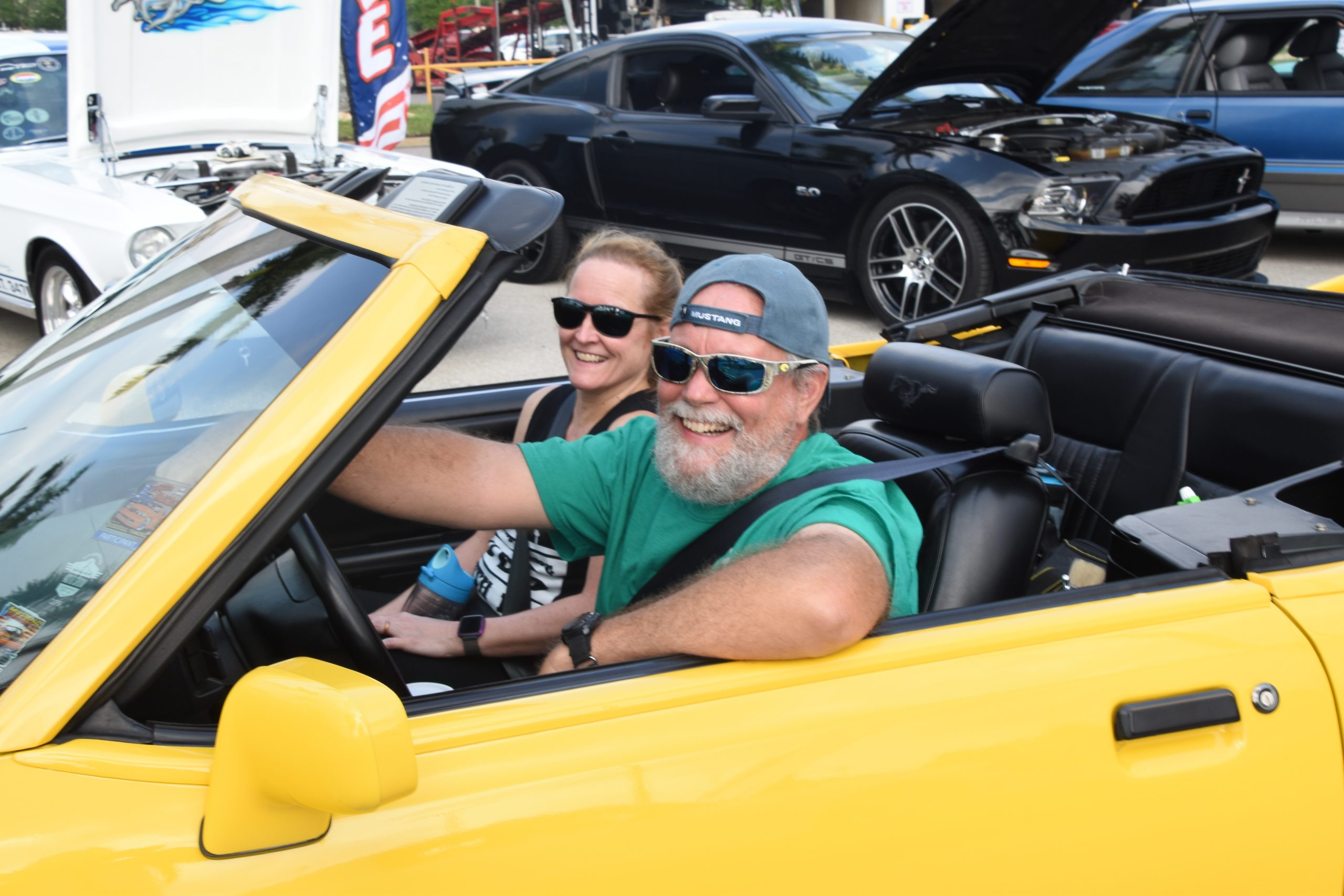 Couple arriving at car show in yellow mustang convertible
